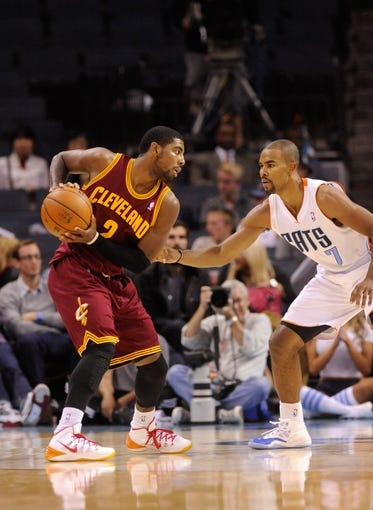 Oct 24, 2013; Charlotte, NC, USA; Cleveland Cavaliers guard Kyrie Irving (2) looks to pass as he is guarded by Charlotte Bobcats guard Ramon Sessions (7) during the game at Time Warner Cable Arena. The Bobcats won 102-95. Mandatory Credit: Sam Sharpe-USA TODAY Sports