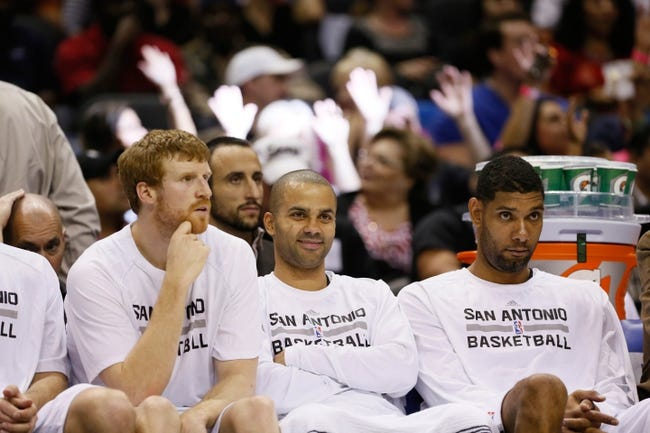 Oct 24, 2013; San Antonio, TX, USA; San Antonio Spurs (from right) Tim Duncan, and Tony Parker, and Matt Bonner watch from the bench during the second half against the Houston Rockets at AT&T Center. The Rockets won 109-92. Mandatory Credit: Soobum Im-USA TODAY Sports