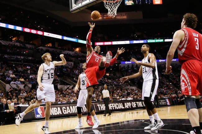 Oct 24, 2013; San Antonio, TX, USA; Houston Rockets center Dwight Howard (12) drives for the basket between San Antonio Spurs forward Matt Bonner (left) and Tim Duncan (right) during the second half at AT&T Center. The Rockets won 109-92. Mandatory Credit: Soobum Im-USA TODAY Sports