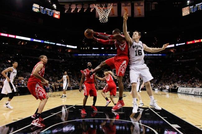 Oct 24, 2013; San Antonio, TX, USA; Houston Rockets center Dwight Howard (12) pulls down a rebound against San Antonio Spurs forward Aron Baynes (16) during the second half at AT&T Center. The Rockets won 109-92. Mandatory Credit: Soobum Im-USA TODAY Sports