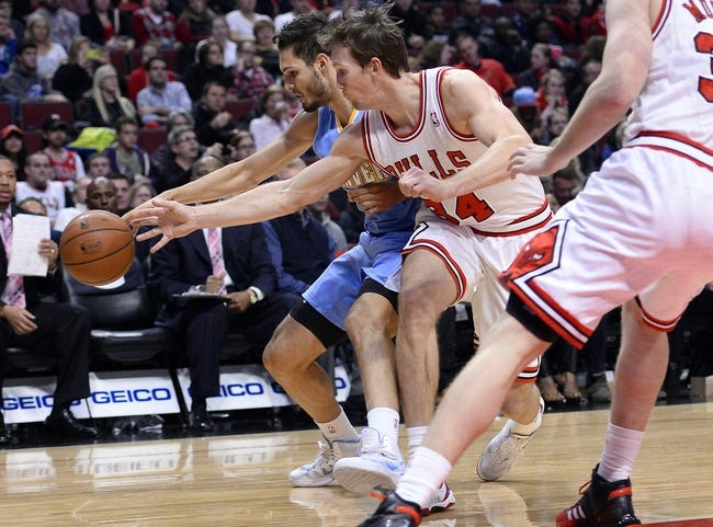 Oct 25, 2013; Chicago, IL, USA; Denver Nuggets shooting guard Evan Fournier (94) and Chicago Bulls shooting guard Mike Dunleavy (34) attempt to get a loose ball  during the second quarter at the United Center. Mandatory Credit: Mike DiNovo-USA TODAY Sports