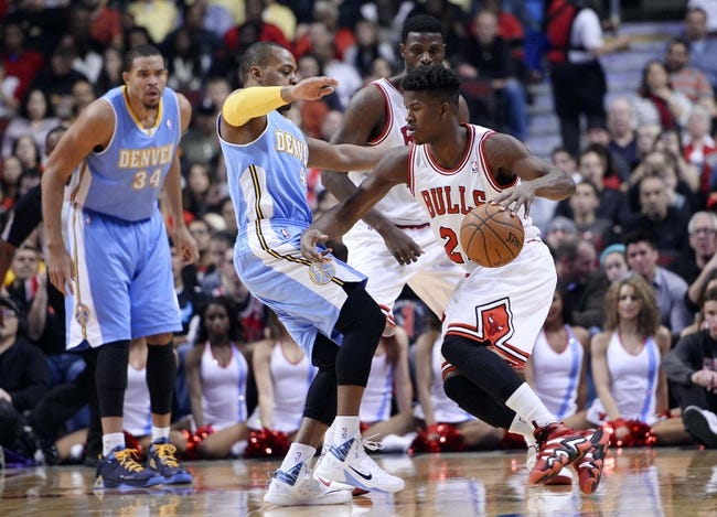 Oct 25, 2013; Chicago, IL, USA; Chicago Bulls shooting guard Jimmy Butler (21) dribbles the ball against Denver Nuggets point guard Randy Foye (4) during the first quarter at the United Center. Mandatory Credit: Mike DiNovo-USA TODAY Sports