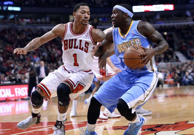 Oct 25, 2013; Chicago, IL, USA; Denver Nuggets point guard Ty Lawson (3) dribbles the ball against Chicago Bulls point guard Derrick Rose (1) during the first quarter at the United Center. Mandatory Credit: Mike DiNovo-USA TODAY Sports