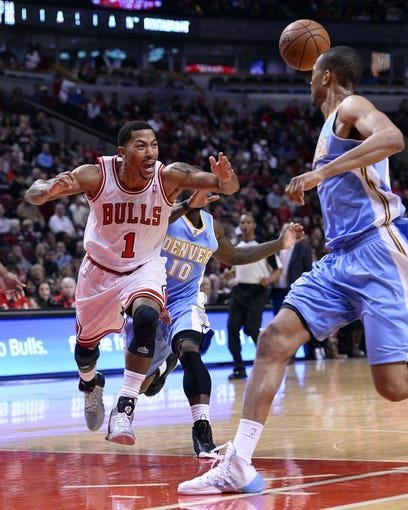Oct 25, 2013; Chicago, IL, USA; Chicago Bulls point guard Derrick Rose (1) is fouled by Denver Nuggets point guard Nate Robinson (10) during the second half at the United Center. Chicago defeats Denver 94-89. Mandatory Credit: Mike DiNovo-USA TODAY Sports