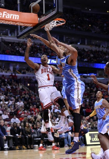 Oct 25, 2013; Chicago, IL, USA; Chicago Bulls point guard Derrick Rose (1) shoots the ball against Denver Nuggets center JaVale McGee (34) during the second half at the United Center. Chicago defeats Denver 94-89. Mandatory Credit: Mike DiNovo-USA TODAY Sports