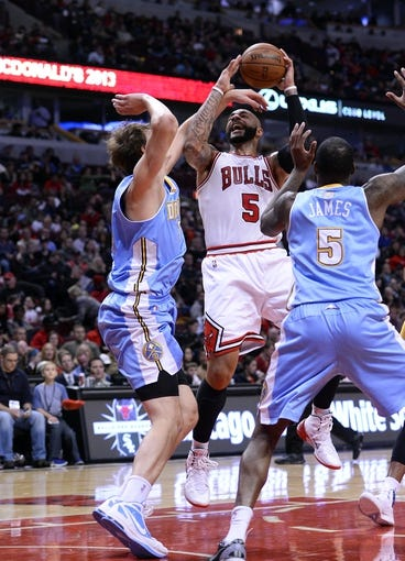 Oct 25, 2013; Chicago, IL, USA; Chicago Bulls power forward Carlos Boozer (5) shoots the ball against Denver Nuggets center Timofey Mozgov (25) during the second half at the United Center. Chicago defeats Denver 94-89. Mandatory Credit: Mike DiNovo-USA TODAY Sports