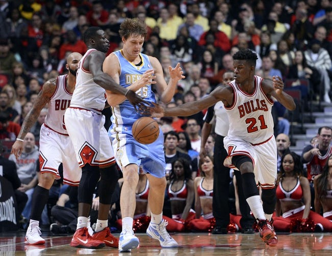 Oct 25, 2013; Chicago, IL, USA; Chicago Bulls shooting guard Jimmy Butler (21) steals the ball from Denver Nuggets center Timofey Mozgov (25) during the second half at the United Center. Chicago defeats Denver 94-89. Mandatory Credit: Mike DiNovo-USA TODAY Sports
