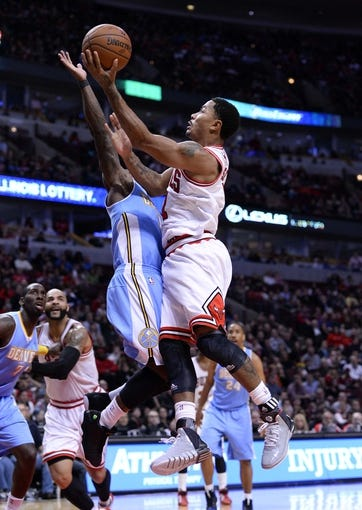 Oct 25, 2013; Chicago, IL, USA; Chicago Bulls point guard Derrick Rose (1) shoots the ball against Denver Nuggets point guard Nate Robinson (10) during the second half at the United Center. Chicago defeats Denver 94-89. Mandatory Credit: Mike DiNovo-USA TODAY Sports