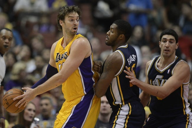Oct 25, 2013; Anaheim, CA, USA; Los Angeles Lakers forward Pau Gasol (16) is defended by Utah Jazz forward Derrick Favors (15) during the second quarter at Honda Center. Mandatory Credit: Kelvin Kuo-USA TODAY Sports