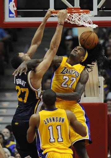 Oct 25, 2013; Anaheim, CA, USA; Utah Jazz center Rudy Gobert (27) dunks the ball while defended by Los Angeles Lakers center Jordan Hill (27) during the fourth quarter at Honda Center. The Los Angeles Lakers defeated the Utah Jazz 111-106. Mandatory Credit: Kelvin Kuo-USA TODAY Sports