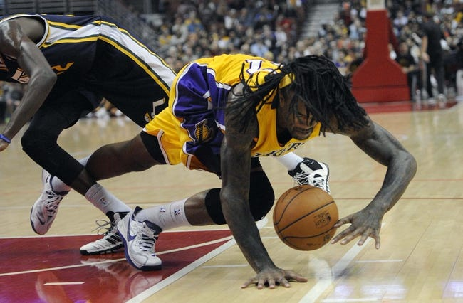 Oct 25, 2013; Anaheim, CA, USA; Los Angeles Lakers center Jordan Hill (27) is tripped up by Utah Jazz guard Justin Holiday (22) during the fourth quarter at Honda Center. The Los Angeles Lakers defeated the Utah Jazz 111-106. Mandatory Credit: Kelvin Kuo-USA TODAY Sports