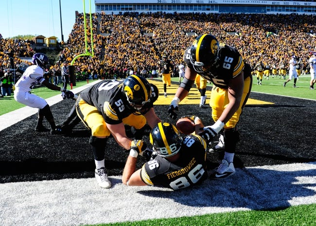 Oct 26, 2013; Iowa City, IA, USA; Iowa Hawkeyes offensive linemen Conor Boffeli (59) and Jordan Walsh (65) help up tight end C.J. Fiedorowicz (86) after Fiedorowicz caught a touchdown pass in overtime against the Northwestern Wildcats at Kinnick Stadium. Iowa won 17-10. Mandatory Credit: Byron Hetzler-USA TODAY Sports