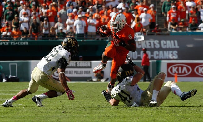 Oct 26, 2013; Miami Gardens, FL, USA; Miami Hurricanes running back Duke Johnson (8) leaps over Wake Forest Demon Deacons linebacker Mike Olson (41) as safety Ryan Janvion (22) moves defends in the second half at Sun Life Stadium. Miami won 24-21. Mandatory Credit: Robert Mayer-USA TODAY Sports