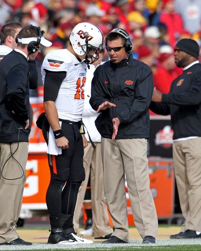 Oct 26, 2013; Ames, IA, USA; Oklahoma State Cowboys quarterback Clint Chelf (10) talks with head coach Mike Gundy during the first quarter against the Iowa State Cyclones at Jack Trice Stadium. Oklahoma State defeated Iowa State 58-27. Mandatory Credit: Brace Hemmelgarn-USA TODAY Sports