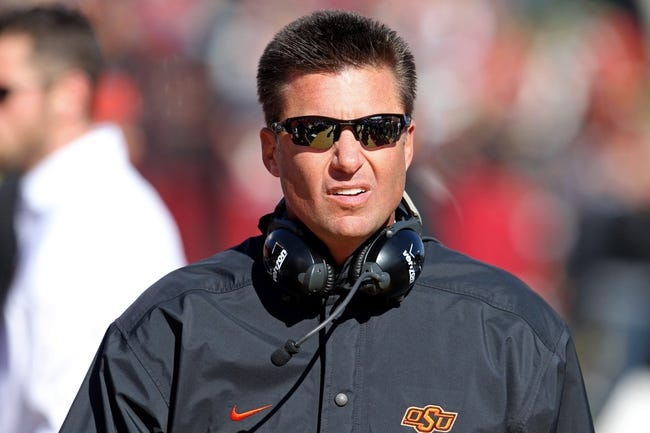 Oct 26, 2013; Ames, IA, USA; Oklahoma State Cowboys head coach Mike Gundy looks on during the first quarter against the Iowa State Cyclones at Jack Trice Stadium. Oklahoma State defeated Iowa State 58-27. Mandatory Credit: Brace Hemmelgarn-USA TODAY Sports