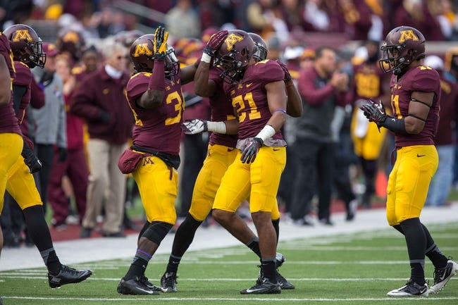 Oct 26, 2013; Minneapolis, MN, USA; Minnesota Golden Gophers defensive back Brock Vereen (21) gets congratulated by Minnesota Golden Gophers linebacker Jephte Matilus (34) after making a tackle in the second half against the Nebraska Cornhuskers at TCF Bank Stadium. The Gophers won 34-23. Mandatory Credit: Jesse Johnson-USA TODAY Sports