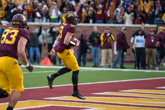 Oct 26, 2013; Minneapolis, MN, USA; Minnesota Golden Gophers quarterback Philip Nelson (9) runs in for a touchdown in the second half against the Nebraska Cornhuskers at TCF Bank Stadium. The Gophers won 34-23. Mandatory Credit: Jesse Johnson-USA TODAY Sports