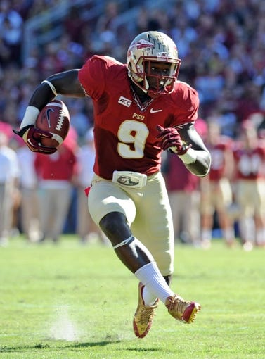 Oct 26, 2013; Tallahassee, FL, USA; Florida State Seminoles running back Karlos Williams (9) runs the ball during the first quarter of the game against the North Carolina State Wolfpack at Doak Campbell Stadium. Mandatory Credit: Melina Vastola-USA TODAY Sports