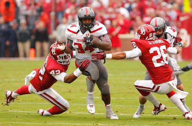 Oct 26, 2013; Norman, OK, USA; Texas Tech Red Raiders running back Kenny Williams (34) attempts to break a tackle by Oklahoma Sooners linebacker Jordan Evans (26) and Dominique Alexander (42) during the first quarter at Gaylord Family - Oklahoma Memorial Stadium. Mandatory Credit: Alonzo Adams-USA TODAY Sports