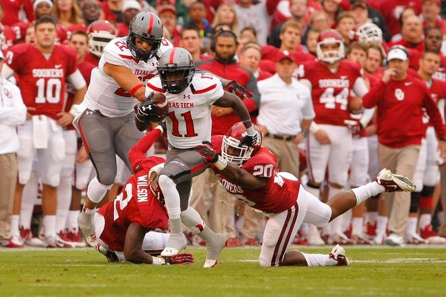 Oct 26, 2013; Norman, OK, USA; Texas Tech Red Raiders wide receiver Jakeem Grant (11) attempts to break a tackle by Oklahoma Sooners Frank Shannon (20) during the first quarter at Gaylord Family - Oklahoma Memorial Stadium. Mandatory Credit: Alonzo Adams-USA TODAY Sports