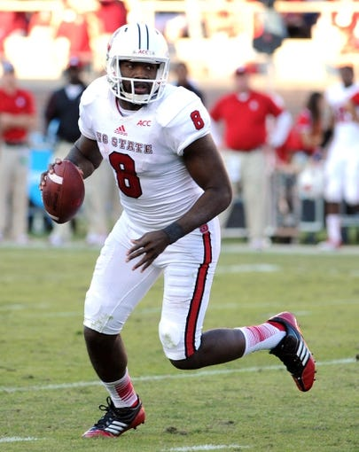 Oct 26, 2013; Tallahassee, FL, USA; North Carolina State Wolfpack quarterback Brandon Mitchell (8) looks to throw the ball during the second half of the game against the Florida State Seminoles at Doak Campbell Stadium. Mandatory Credit: Melina Vastola-USA TODAY Sports