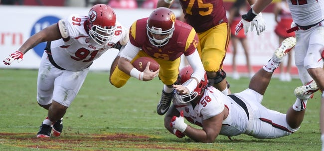 Oct 26, 2013; Los Angeles, CA, USA; USC Trojans quarterback Cody Kessler (6) dives for extra yards as Utah Utes defensive tackle Tenny Palepoi (91) and Utah Utes defensive tackle LT Tuipulotu (58) try to stop him during fourth quarter action at Los Angeles Memorial Coliseum. The Trojans went on to a 19-3 win. Mandatory Credit: Robert Hanashiro-USA TODAY Sports