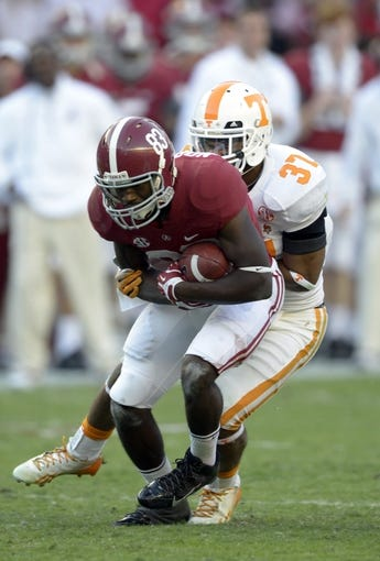 Oct 26, 2013; Tuscaloosa, AL, USA; Alabama Crimson Tide wide receiver Kevin Norwood (83) gets wrapped up by Tennessee Volunteers defensive back Brian Randolph (37) on a reception during the fourth quarter at Bryant-Denny Stadium. Mandatory Credit: John David Mercer-USA TODAY Sports