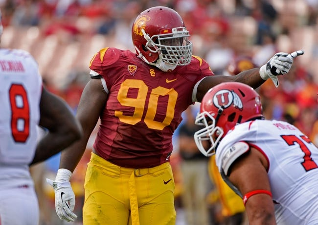 Oct 26, 2013; Los Angeles, CA, USA; USC Trojans defensive end George Uko (90) points across the kin be of scrimmage to the Utah Utes offense during fourth quarter action at Los Angeles Memorial Coliseum. The Trojans won 19-3. Mandatory Credit: Robert Hanashiro-USA TODAY Sports