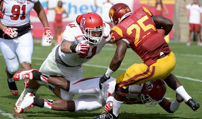 Oct 26, 2013; Los Angeles, CA, USA; Utah Utes linebacker Jared Norris (41) makes a diving tackle to stop USC Trojans running back Silas Redd (25) during first half at Los Angeles Memorial Coliseum. Also on the play is Utah Utes defensive back Michael Walker (15). The Trojans won 19-3. Mandatory Credit: Robert Hanashiro-USA TODAY Sports
