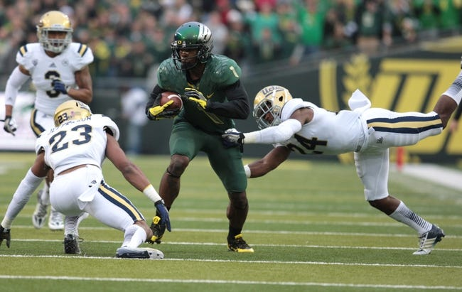 Oct 26, 2013; Eugene, OR, USA; UCLA Bruins cornerback Anthony Jefferson (23) and UCLA Bruins cornerback Ishmael Adams (24) reach out to tackle Oregon Ducks wide receiver Josh Huff (1) at Autzen Stadium. Mandatory Credit: Scott Olmos-USA TODAY Sports