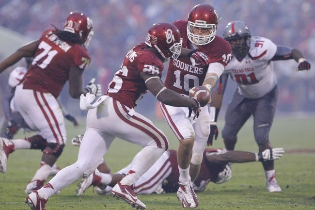 Oct 26, 2013; Norman, OK, USA; Oklahoma quarterback Blake Bell (10) hands off the ball to running back Damien Williams (26) during the third quarter against the Texas Tech at Gaylord Family - Oklahoma Memorial Stadium. Oklahoma won 38-30.  Mandatory Credit: Alonzo Adams-USA TODAY Sports
