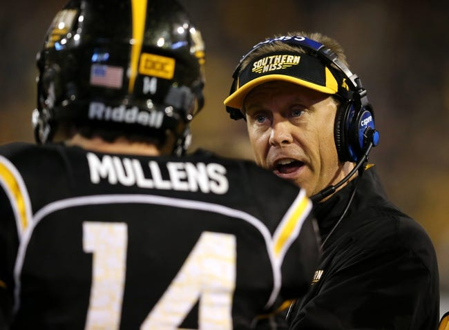 Oct 26, 2013; Hattiesburg, MS, USA; Southern Miss Golden Eagles head coach Todd Monken (right) talks to freshman quarterback Nick Mullens (14) in the second quarter of their game against the North Texas Mean Green at M.M. Roberts Stadium. Mandatory Credit: Chuck Cook-USA TODAY Sports