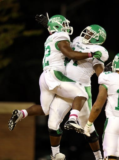 Oct 26, 2013; Hattiesburg, MS, USA; North Texas Mean Green running back Antoinne Jimmerson (22) celebrates a touchdown run with offensive linesman LaChris Anyiam (64) in the second quarter of their game against the Southern Miss Golden Eagles at M.M. Roberts Stadium. Mandatory Credit: Chuck Cook-USA TODAY Sports