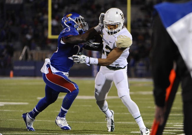 Oct 26, 2013; Lawrence, KS, USA; Kansas Jayhawks safety Dexter Linton (23) pushes Baylor Bears wide receiver Levi Norwood (42) out of bounds in the first half at Memorial Stadium. Mandatory Credit: John Rieger-USA TODAY Sports