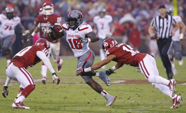 Oct 26, 2013; Norman, OK, USA; Texas Tech Red Raiders wide receiver Jameon Lewis (4) attempts to break a tackle by Oklahoma Sooners cornerback Fred Tiller (3) during the third quarter at Gaylord Family - Oklahoma Memorial Stadium. Oklahoma won 38-30.  Mandatory Credit: Alonzo Adams-USA TODAY Sports