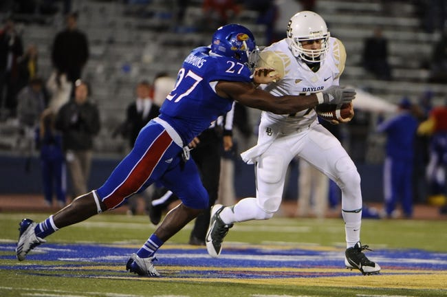 Oct 26, 2013; Lawrence, KS, USA; Baylor Bears quarterback Seth Russell (17) is tackled by Kansas Jayhawks linebacker Victor Simmons (27) in the second half at Memorial Stadium. Baylor won 59-14. Mandatory Credit: John Rieger-USA TODAY Sports