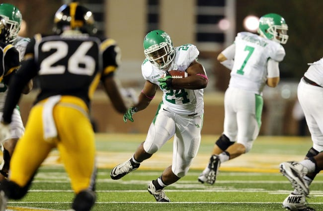 Oct 26, 2013; Hattiesburg, MS, USA; North Texas Mean Green running back Brandin Byrd (24) runs against the Southern Miss Golden Eagles defense in the second half of their game at M.M. Roberts Stadium. North Texas won, 55-14. Mandatory Credit: Chuck Cook-USA TODAY Sports