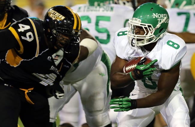 Oct 26, 2013; Hattiesburg, MS, USA; North Texas Mean Green running back Mark Lewis (8) runs past Southern Miss Golden Eagles defensive lineman Adam Williams (49) in the second half at M.M. Roberts Stadium. North Texas won 55-14. Mandatory Credit: Chuck Cook-USA TODAY Sports