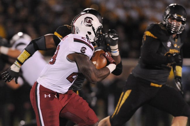 Oct 26, 2013; Columbia, MO, USA; South Carolina Gamecocks running back Mike Davis (28) runs with the ball as Missouri Tigers defensive lineman Michael Sam (52) attempts to tackle during the second half at Faurot Field. South Carolina won 27-24. Mandatory Credit: Denny Medley-USA TODAY Sports