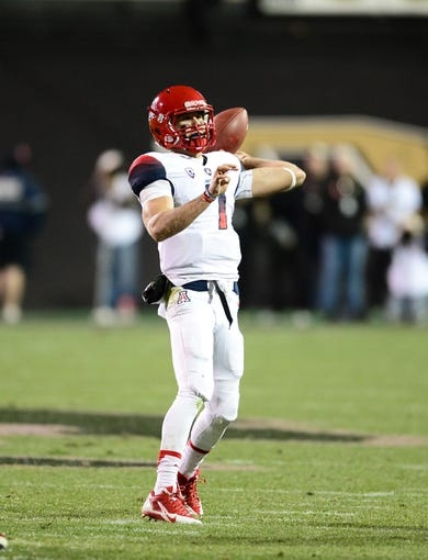 Oct 26, 2013; Boulder, CO, USA; Arizona Wildcats quarterback B.J. Denker (7) prepares to pass in the second quarter against the Colorado Buffaloes at Folsom Field. Mandatory Credit: Ron Chenoy-USA TODAY Sports