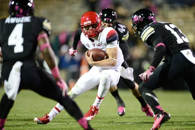 Oct 26, 2013; Boulder, CO, USA; Arizona Wildcats quarterback B.J. Denker (7) scrambles with the ball in the third quarter against the Colorado Buffaloes at Folsom Field. The Wildcats won 44-20. Mandatory Credit: Ron Chenoy-USA TODAY Sports