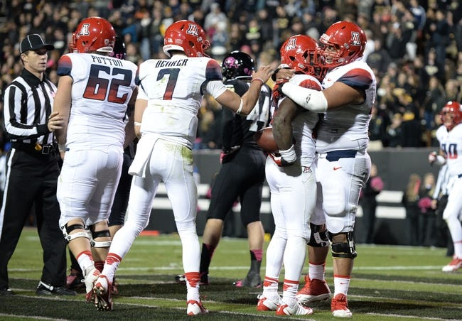 Oct 26, 2013; Boulder, CO, USA; Arizona Wildcats running back Ka'Deem Carey (center) is congratulated for his touchdown by offensive linesman Steven Gurrola (56) and quarterback B.J. Denker (7) and offensive linesman Chris Putton (62) in the third quarter against the Colorado Buffaloes at Folsom Field. The Wildcats defeated the Buffaloes 44-20. Mandatory Credit: Ron Chenoy-USA TODAY Sports