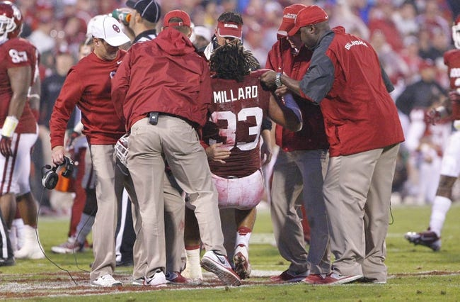 Oct 26, 2013; Norman, OK, USA; Oklahoma Sooners player Trey Millard is helped up after being injured in a play against the Texas Tech Red Raiders during the fourth quarter at Gaylord Family - Oklahoma Memorial Stadium. Oklahoma won 38-30.  Mandatory Credit: Alonzo Adams-USA TODAY Sports