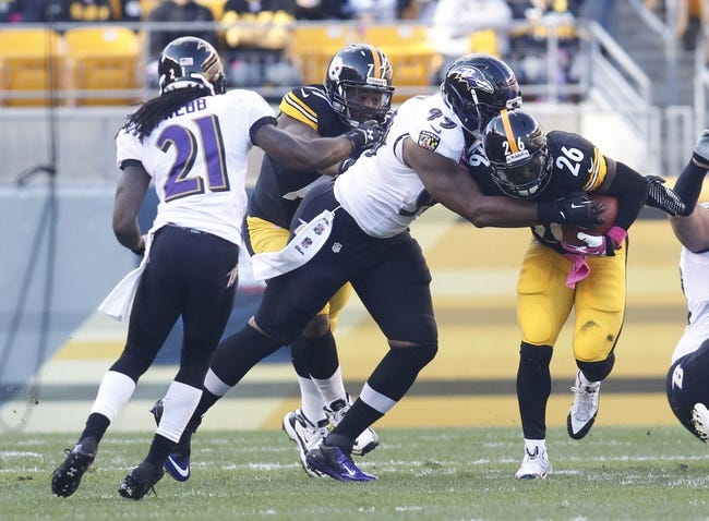 Oct 20, 2013; Pittsburgh, PA, USA; Baltimore Ravens defensive end Chris Canty (99) tackles Pittsburgh Steelers running back Le'Veon Bell (26) during the first quarter at Heinz Field. The Steelers won 19-16. Mandatory Credit: Charles LeClaire-USA TODAY Sports