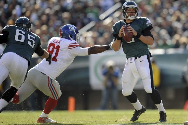 Oct 27, 2013; Philadelphia, PA, USA; Philadelphia Eagles quarterback Matt Barkley (2) eludes New York Giants defensive end Justin Tuck (91) during the first half at Lincoln Financial Field. The Giants won the game 15-7. Mandatory Credit: Joe Camporeale-USA TODAY Sports