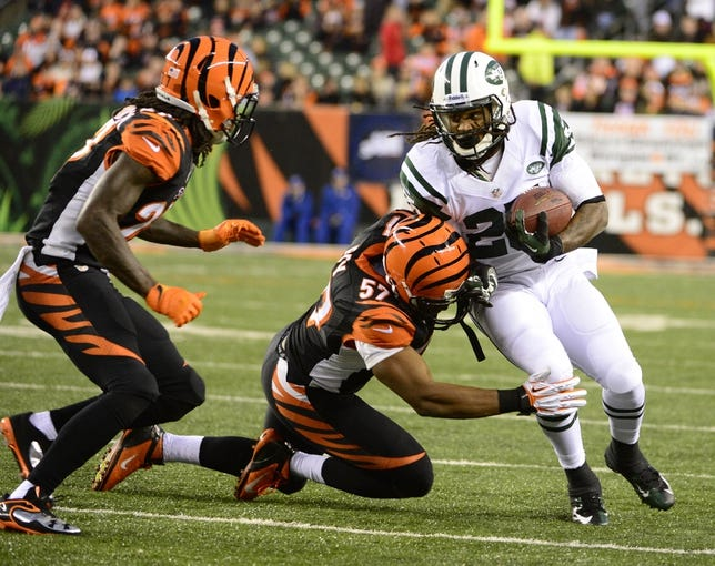 Oct 27, 2013; Cincinnati, OH, USA; New York Jets running back Alex Green (25) gets tackled by Cincinnati Bengals linebacker Vincent Rey (57) during the second half of the game at Paul Brown Stadium. Mandatory Credit: Marc Lebryk-USA TODAY Sports