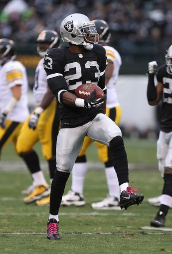 Oct 27, 2013; Oakland, CA, USA; Oakland Raiders cornerback Tracy Porter (23) celebrates after the fumble recovery against the Pittsburgh Steelers during the fourth quarter at O.co Coliseum. The Oakland Raiders defeated the Pittsburgh Steelers 21-18. Mandatory Credit: Kelley L Cox-USA TODAY Sports