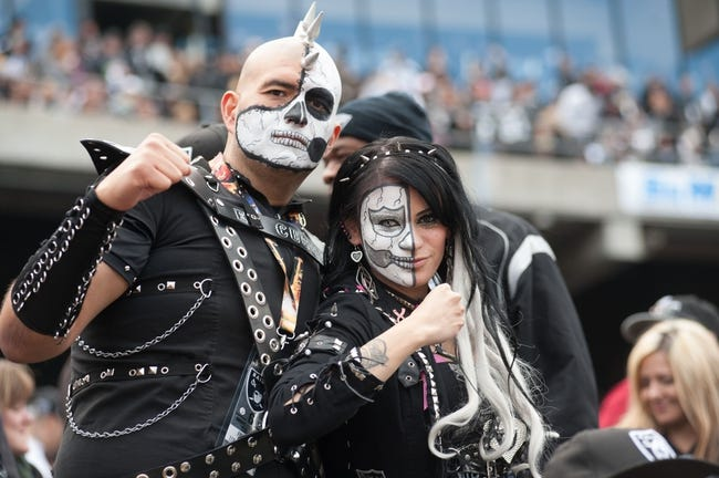 Oct 27, 2013; Oakland, CA, USA; Oakland Raiders fans John Filpa and Cindy Reyna pose for a picture during the game between the Oakland Raiders and Pittsburgh Steelers at O.co Coliseum. The Oakland Raiders defeated the Pittsburgh Steelers 21-18. Mandatory Credit: Ed Szczepanski-USA TODAY Sports