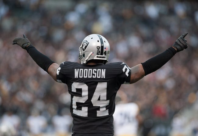 Oct 27, 2013; Oakland, CA, USA; Oakland Raiders free safety Charles Woodson (24) raises his arms after the Oakland Raiders intercepted Pittsburgh Steelers quarterback Ben Roethlisberger (7, not pictured) during the fourth quarter at O.co Coliseum. The Oakland Raiders defeated the Pittsburgh Steelers 21-18. Mandatory Credit: Ed Szczepanski-USA TODAY Sports