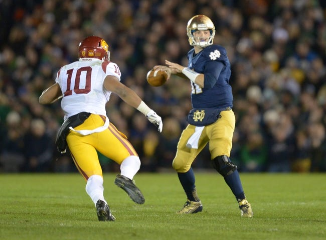 Oct 19, 2013; South Bend, IN, USA; Notre Dame Fighting Irish quarterback Tommy Rees (11) throws a pass under pressure from Southern California Trojans linebacker Hayes Pullard (10) at Notre Dame Stadium. Notre Dame defeated USC 14-10. Mandatory Credit: Kirby Lee-USA TODAY Sports